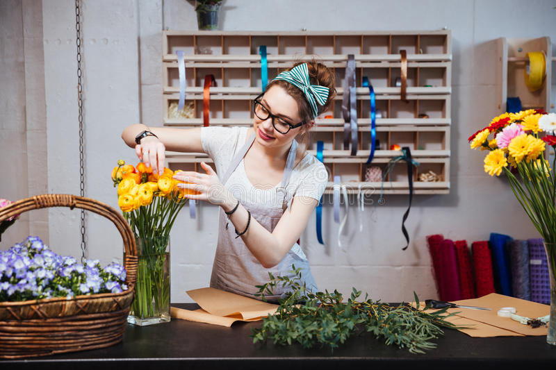 Smiling woman florist taking care of roses in flower shop stock images