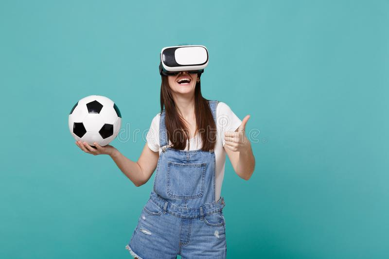 Smiling woman football fan in headset holding soccer ball, showing thumb up isolated on blue turquoise wall background. People emotions, sport family leisure stock image