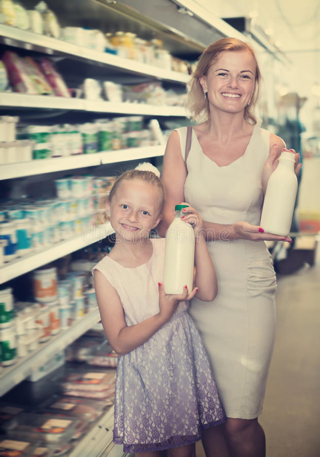 Smiling woman and girl holding bottle with milk royalty free stock photo