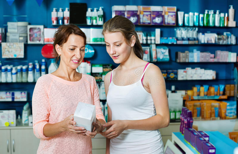 Smiling woman with girl teenager packing body care goods. Smiling glad women with girl teenager packing body care goods in pharmaceutical store royalty free stock image