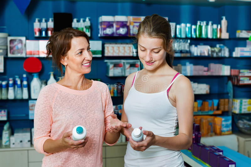 Smiling woman with girl teenager packing body care goods. Positive glad women with girl teenager packing body care goods in pharmaceutical store royalty free stock photography