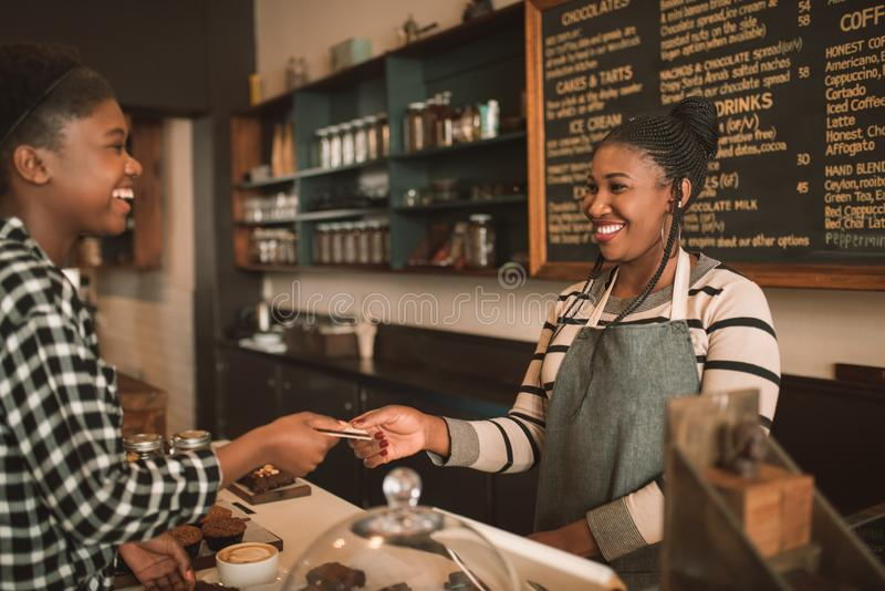 Smiling woman giving her credit card to a cafe barista royalty free stock photography