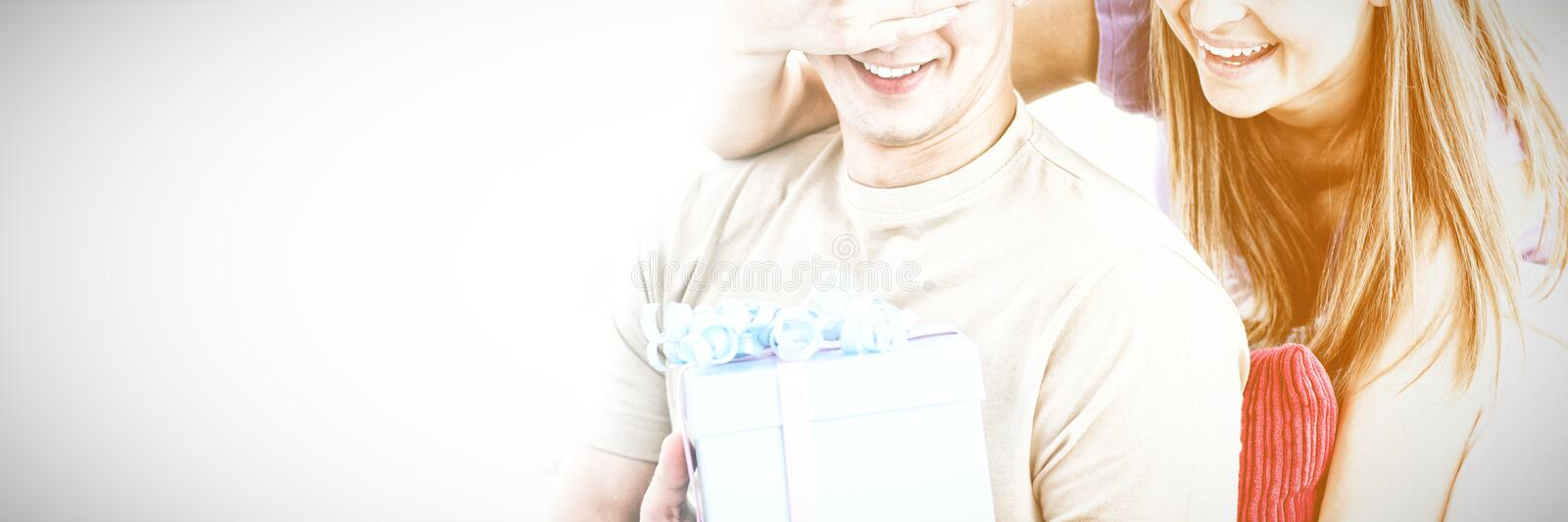Smiling woman giving a present to her boyfriend stock photo
