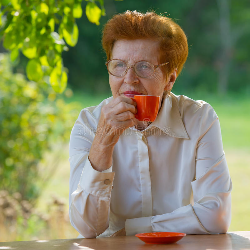 Smiling woman in glasses is drinking coffee outdoors. stock photography