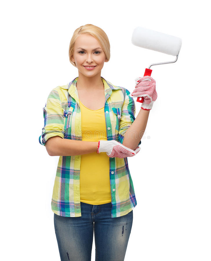 Smiling woman in gloves with paint roller. Repair, construction and maintenance concept - smiling woman in gloves with paint roller royalty free stock photography