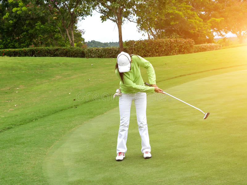 Smiling woman golf player putting successfully ball on green royalty free stock photos
