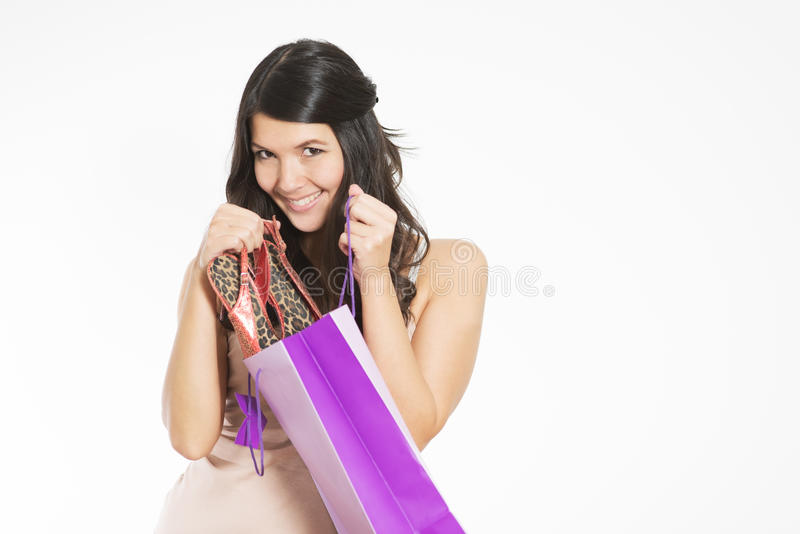 Smiling woman happy with her purchase. Smiling attractive young woman happy with her purchase giving the viewer a sneak peek as she lifts it out of a purple royalty free stock photos
