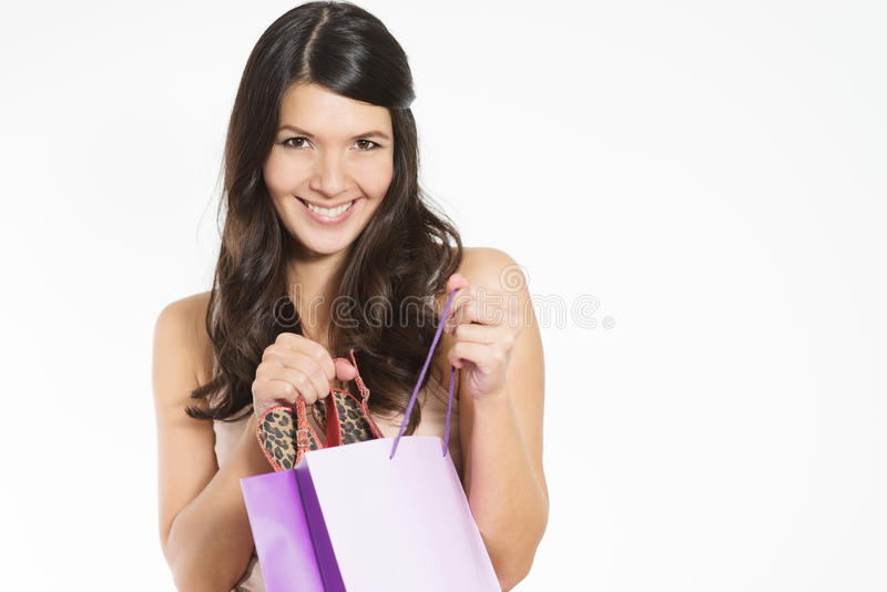 Smiling woman happy with her purchase. Smiling attractive young woman happy with her purchase giving the viewer a sneak peek as she lifts it out of a purple royalty free stock photo