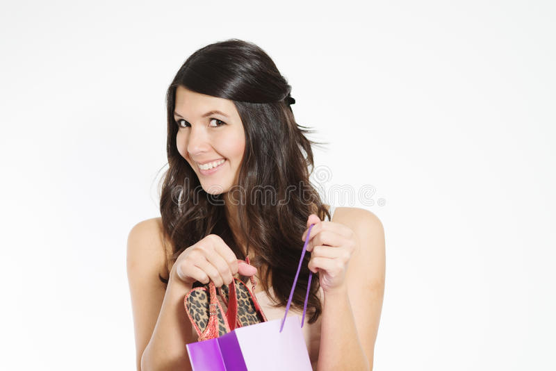 Smiling woman happy with her purchase. Smiling attractive young woman happy with her purchase giving the viewer a sneak peek as she lifts it out of a purple stock photography