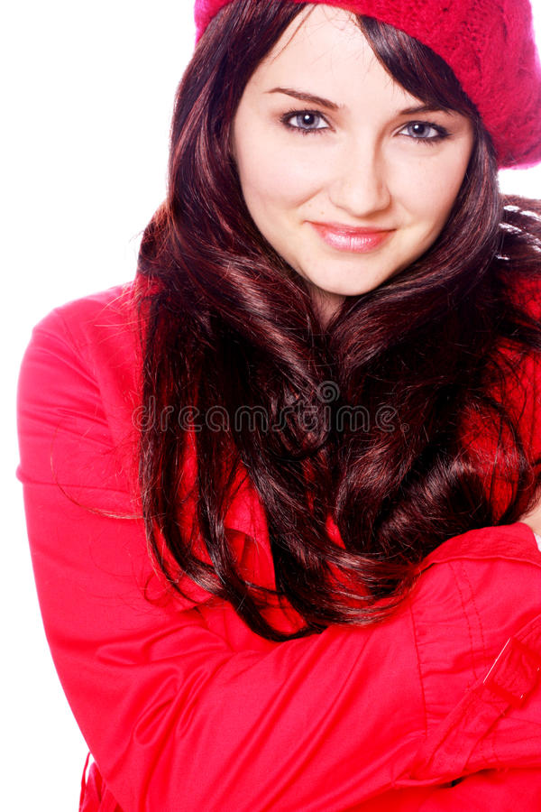 Smiling woman in hat and coat. A smiling young woman wearing a red hat and coat, on a white background stock image