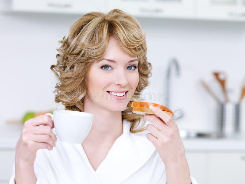 Smiling woman having breakfast royalty free stock image
