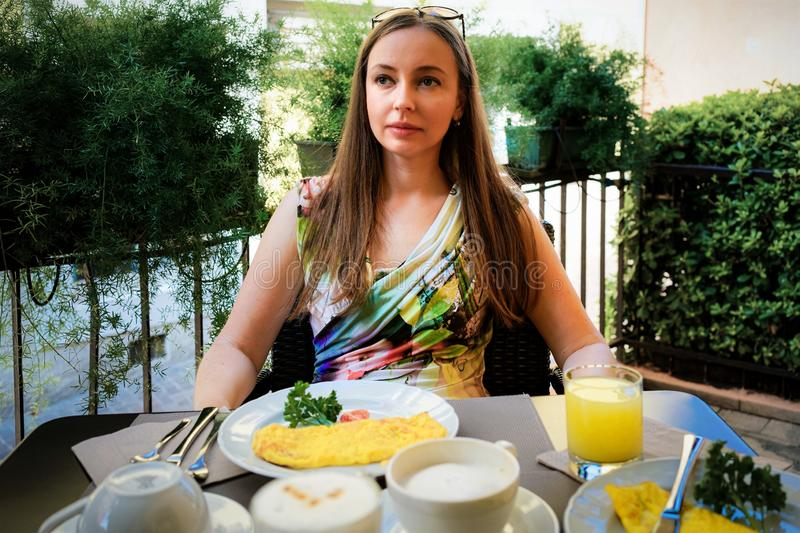 Smiling Woman having breakfast with the omelette royalty free stock photos