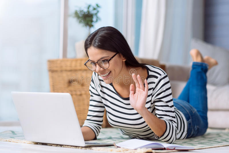 Smiling woman having a conversation via the Internet royalty free stock image