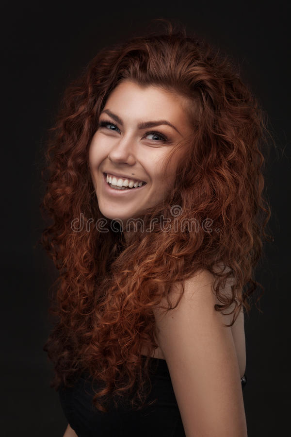 Smiling woman with healthy brown curly hair stock photo