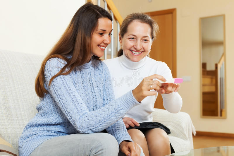 Smiling woman and her daughter with pregnancy test stock images