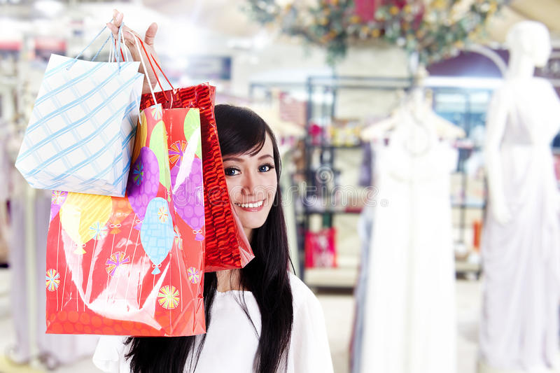 Smiling Woman Hiding Behind Her Shopping Bags Stock Image