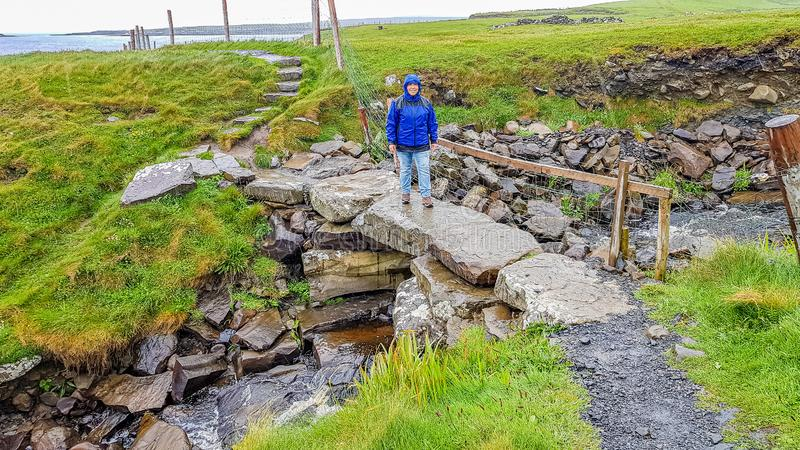 Smiling woman hiking on a stone bridge on the coastal walk route from Doolin to the Cliffs of Moher. Geosites and geopark, Wild Atlantic Way, rainy day in the royalty free stock photography