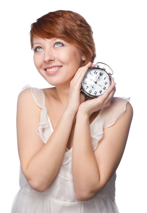 Smiling woman holding alarm clock royalty free stock photo