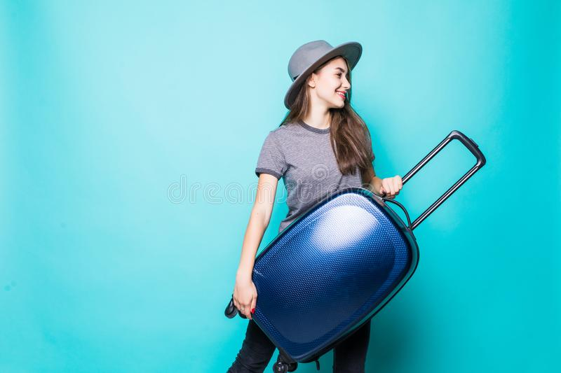 Smiling young woman holding blue suitcase isolated on blue background. Smiling woman holding blue suitcase isolated on blue background royalty free stock image