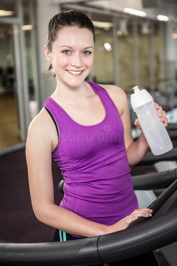 Smiling woman holding bottle of water stock images