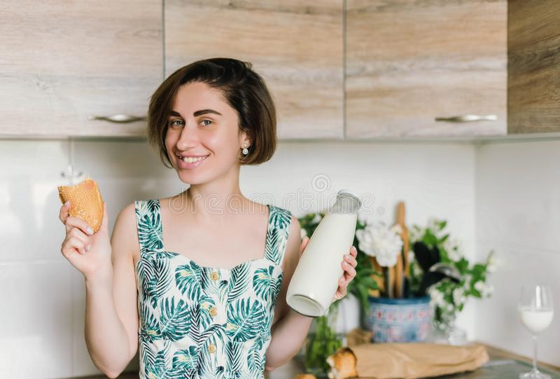 Smiling woman holding bread and milk bottle portrait on kitchen royalty free stock images