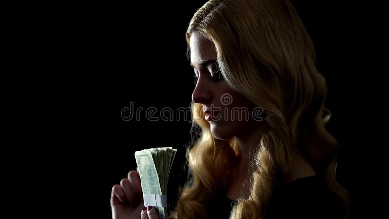 Smiling woman holding bunch of dollars, escort service, love for money concept royalty free stock photo