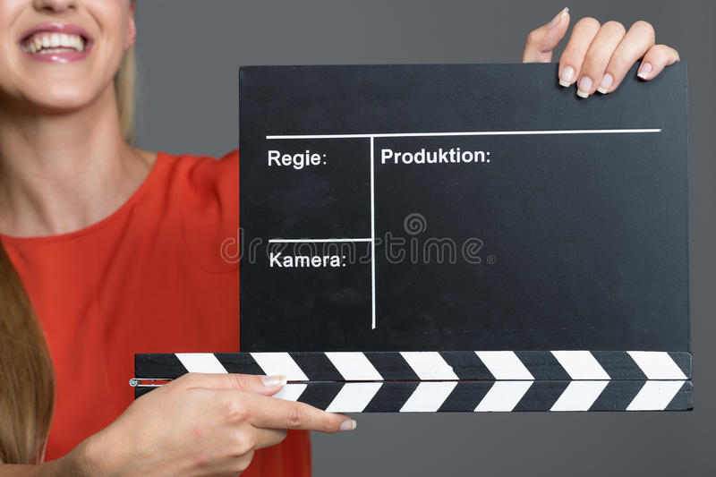 Smiling woman holding a clapperboard. During a film production to give the sound to commence recording of the audio during each new take royalty free stock image