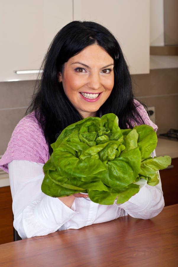 Smiling woman holding fresh lettuce stock image