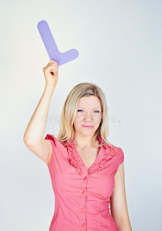 Smiling woman holding the letter L stock photography