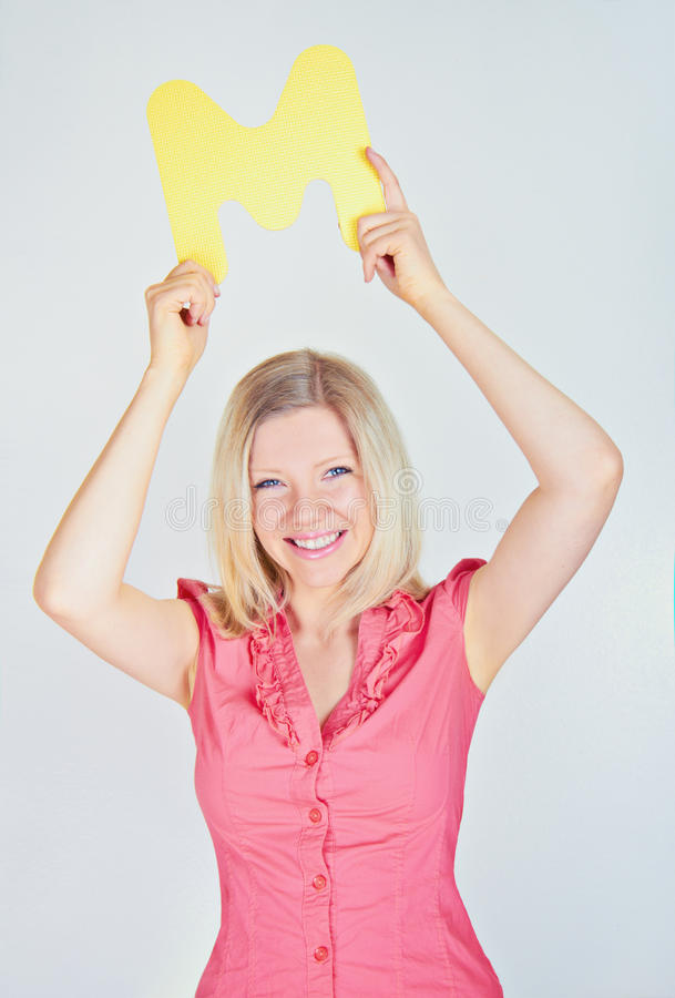 Smiling woman holding the letter M royalty free stock photos