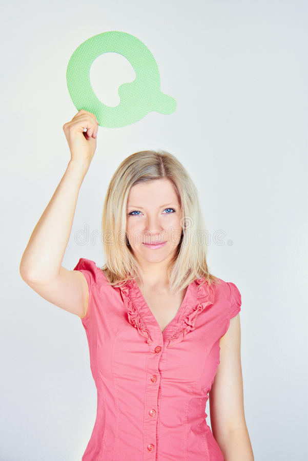 Smiling woman holding the letter Q royalty free stock images