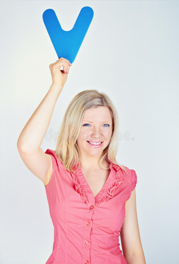 Smiling woman holding the letter V royalty free stock image