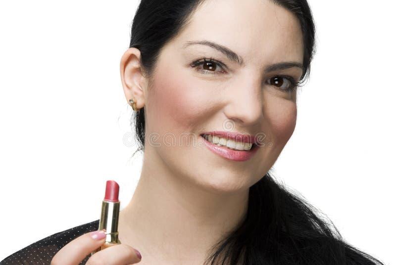 Smiling woman holding lipstick stock photos