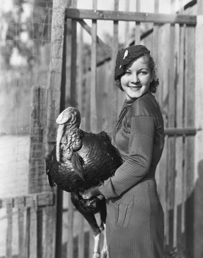 Smiling woman holding live turkey stock photos