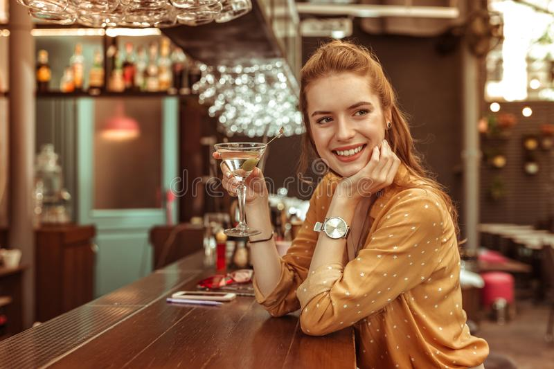 Smiling woman holding martini drink sitting at the bar counter royalty free stock images