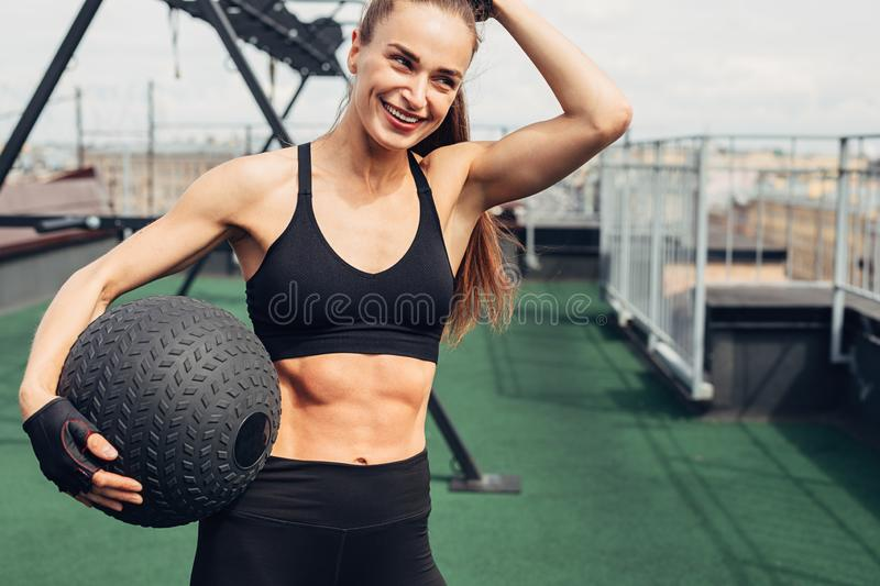 Smiling woman holding a medicine ball royalty free stock image