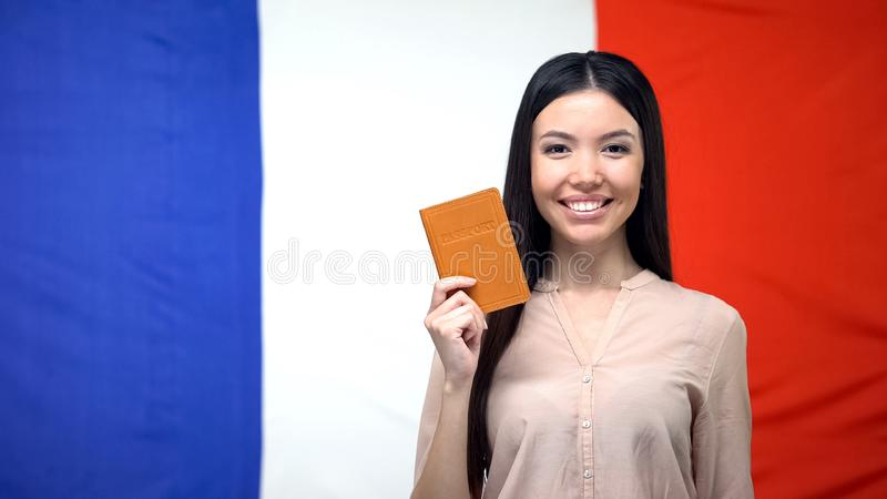 Smiling woman holding passport against French flag background, travel abroad stock image