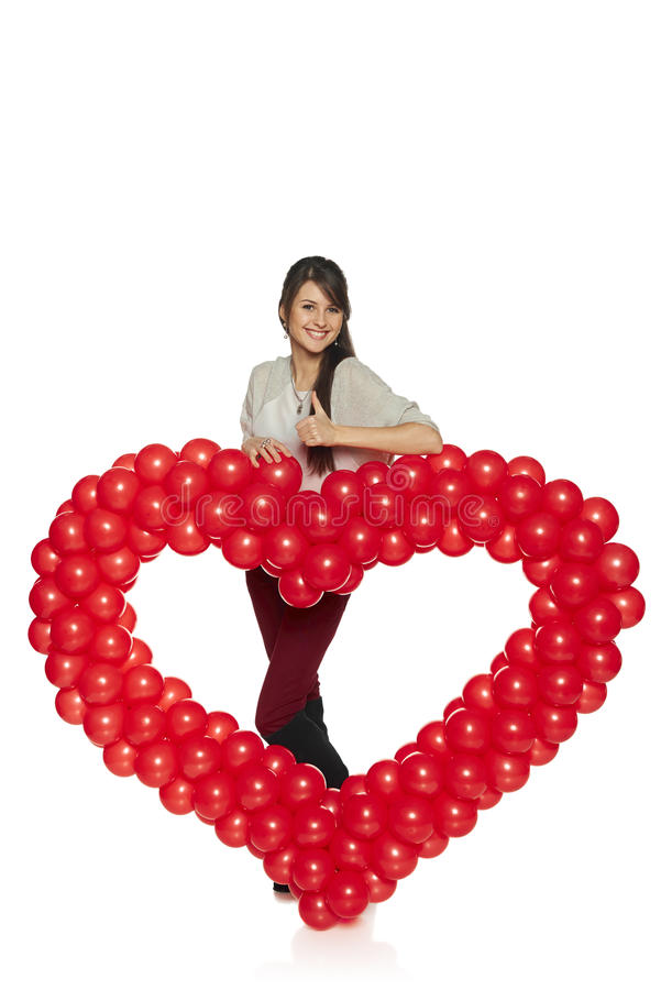 Smiling woman holding red balloon heart stock image
