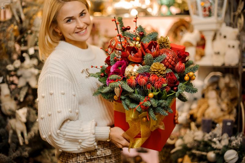 Smiling woman holding a red box with gold tape with different bright flowers decorated with fir-tree branches. In the blurred background of flower shop stock photo