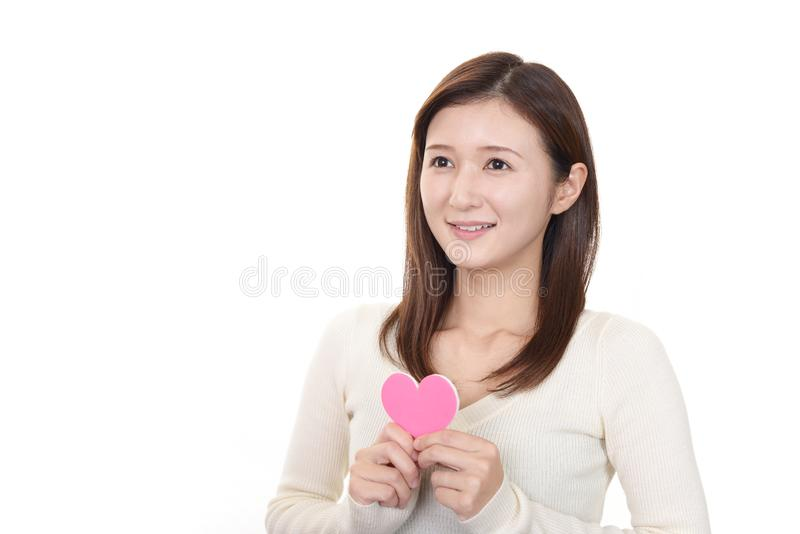 Smiling woman with a pink heart stock photography