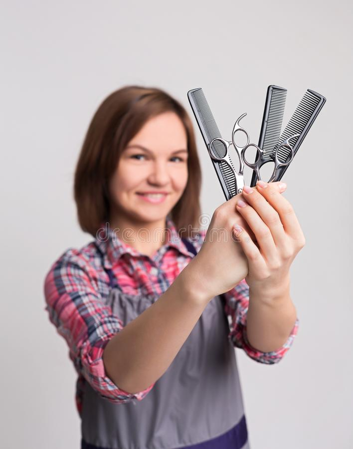 Female hairdresser holding scissors and comb at gray background royalty free stock photos