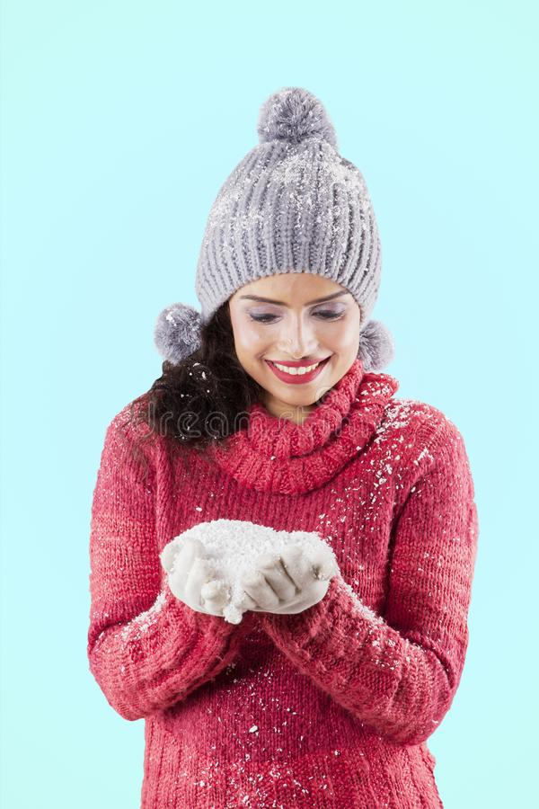 Smiling woman holding snow on her palms royalty free stock photos