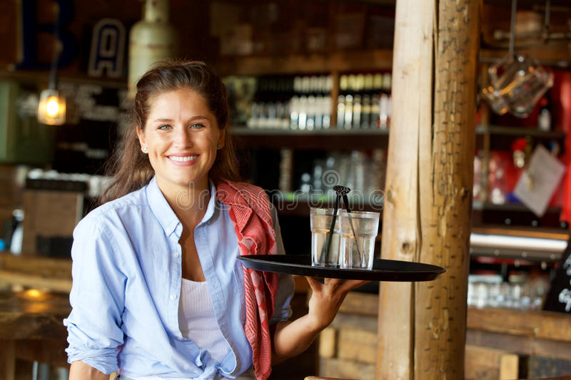 Smiling woman holding tray of drinks at a bar royalty free stock image