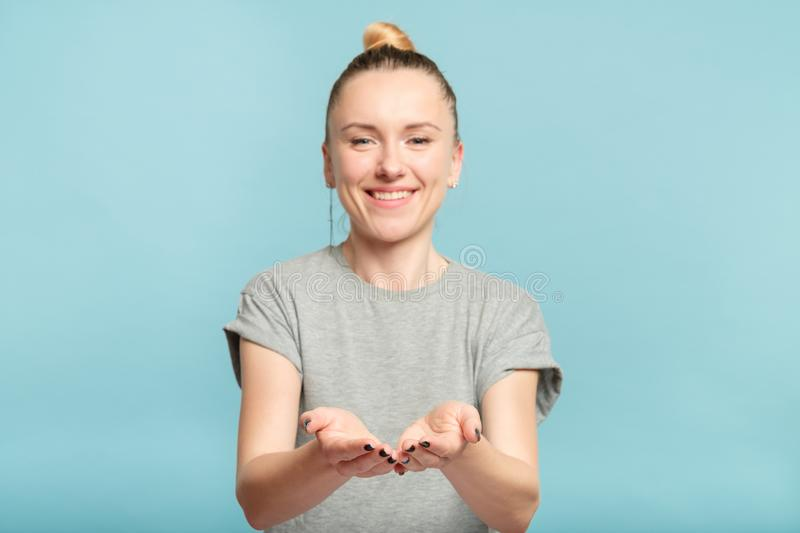 Smiling woman holding virtual object empty palms stock image