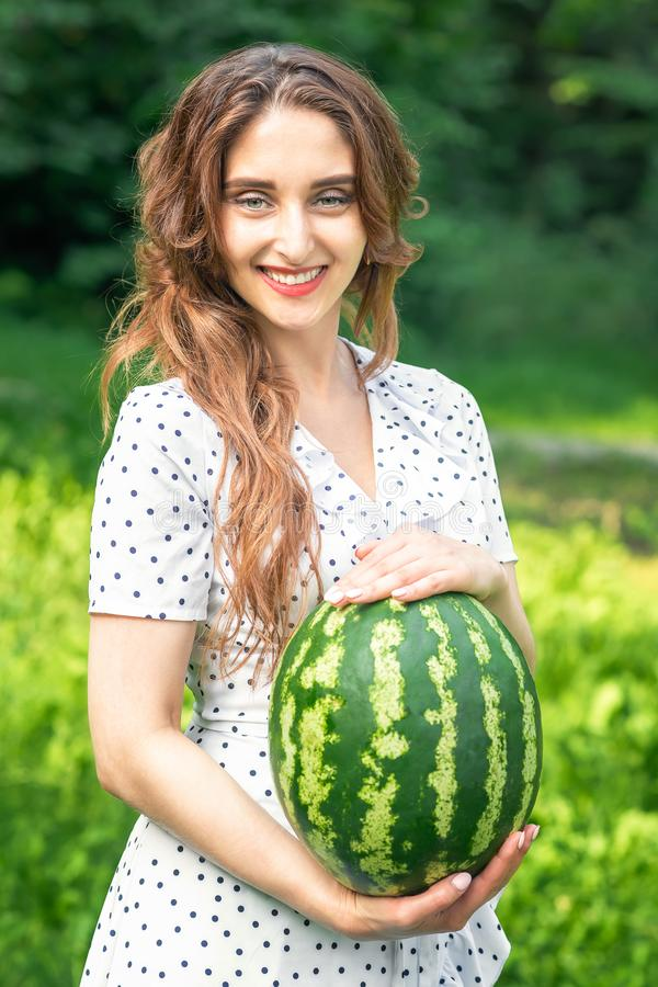 Smiling woman is holding watermelon in white dress on green nature background royalty free stock photography
