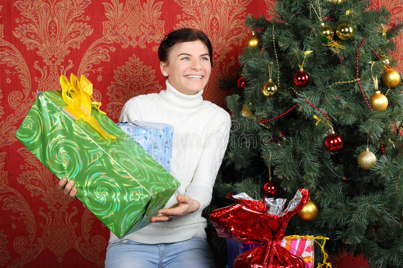 Smiling woman holds gifts near Christmas tree. And looks up at home royalty free stock photography