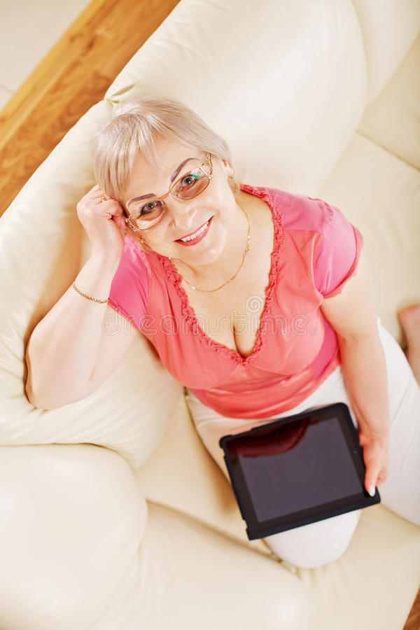 Smiling woman at home holding tablet PC royalty free stock images