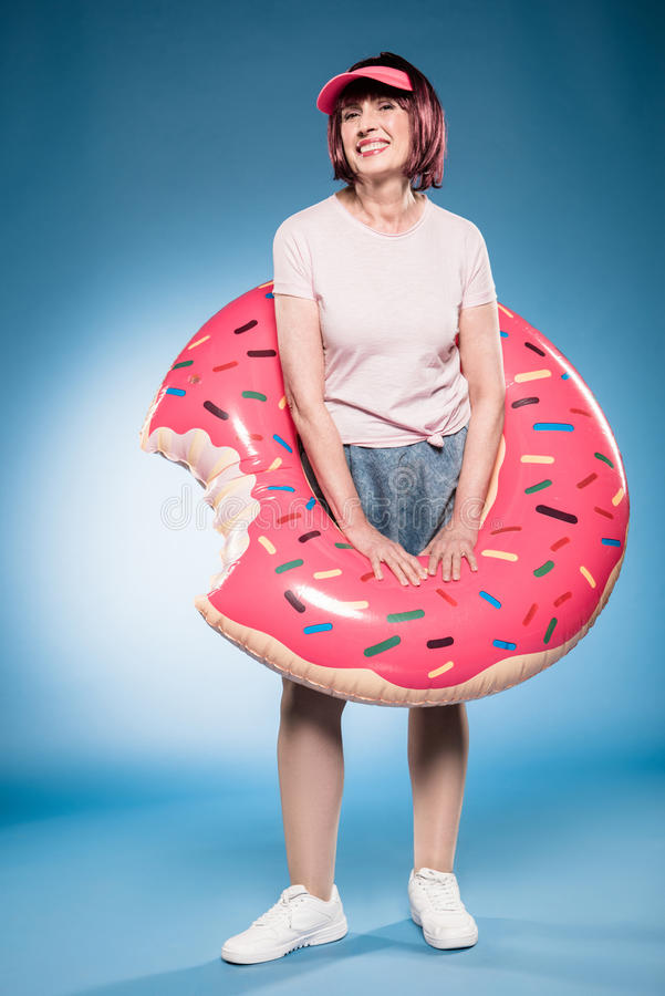 Smiling woman with inflatable mattress in hands looking at camera stock photo