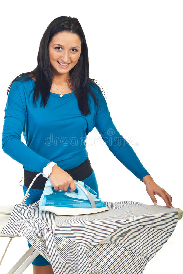 Smiling woman ironing a shirt stock image