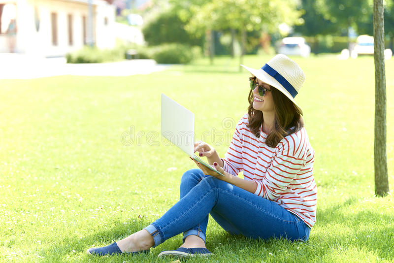 Smiling woman with laptop outdoor stock photography
